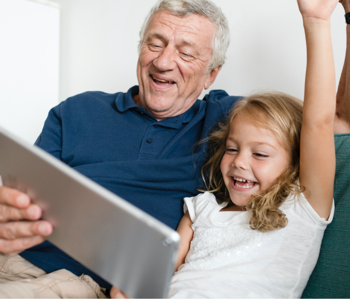 Grandfather and granddaughter having fun over a tablet.