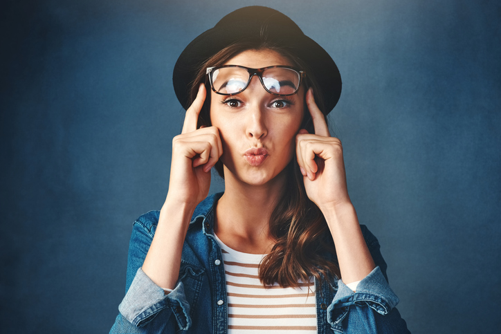 Pretty young woman with glasses on her forehead, pointing on her temples like she had a great idea.